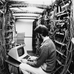 Man in computer room with older style terminal computer