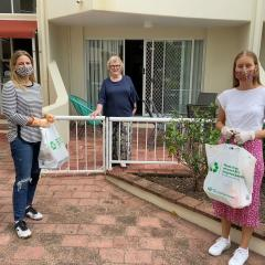 Shopping Angels co-founders Julian Corvin (left) and Tara O'Kane (right) deliver groceries to Cherese, who is self-isolating on the Gold Coast.